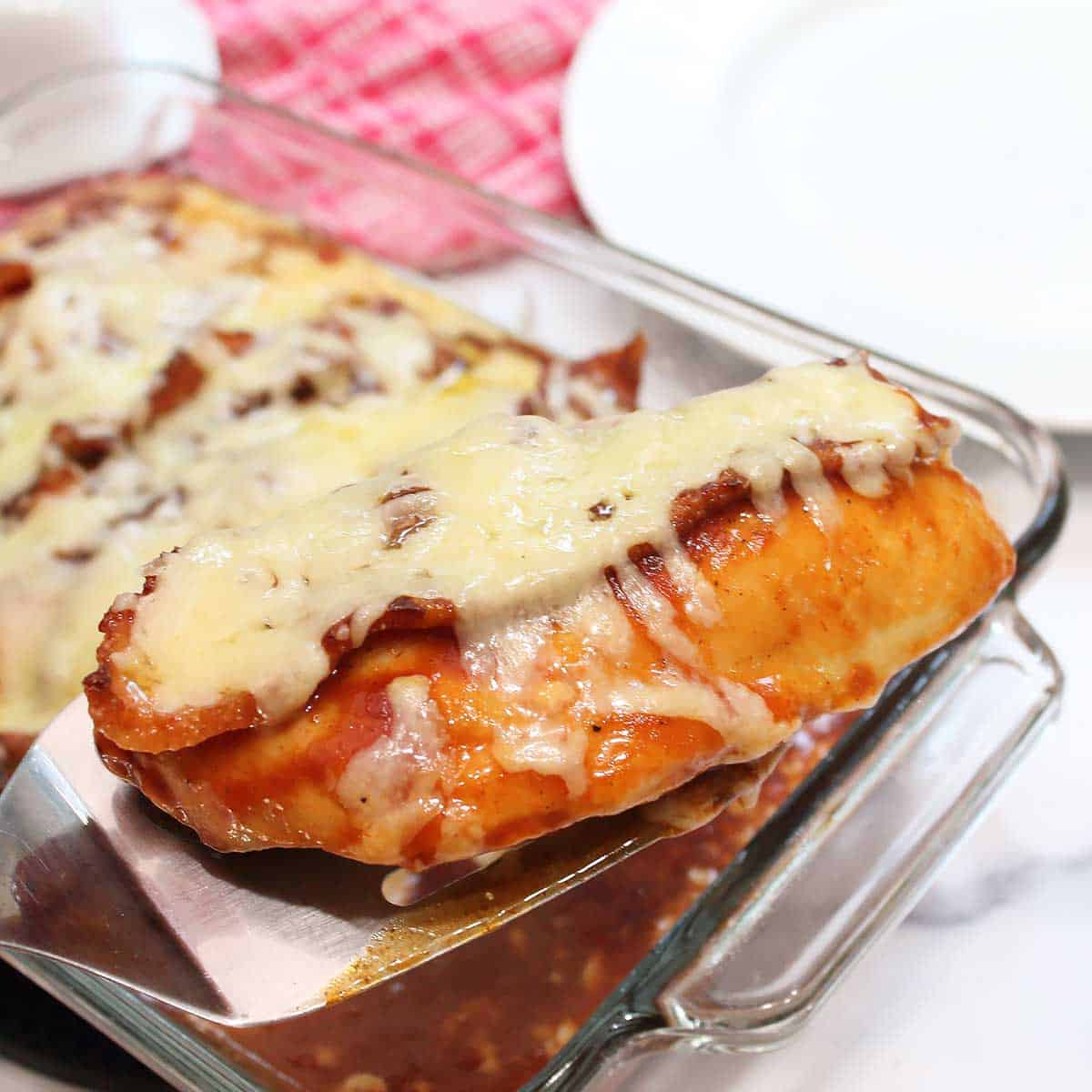 Lifting baked chicken breast out of baking dish.
