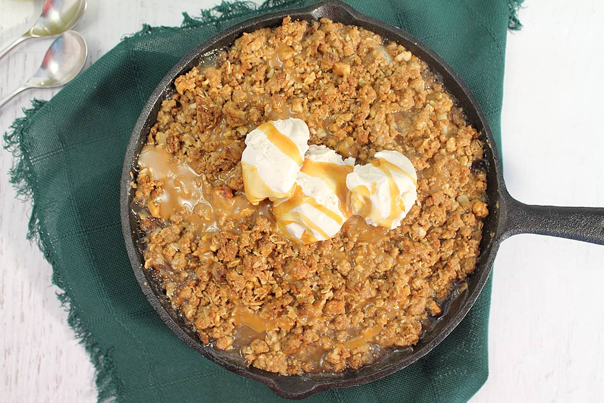 Overhead of baked crisp with ice cream and caramel drizzle.