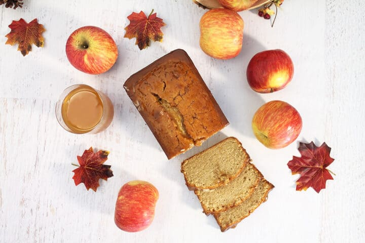 Overhead of sliced apple cider cake on white table with apples and fall leaves surrounding it.
