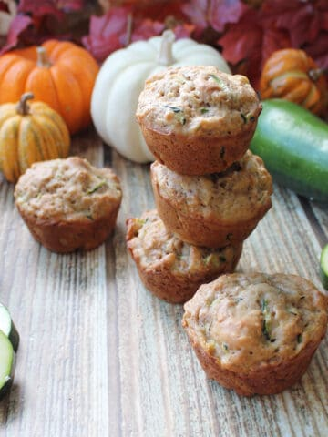 Stacked muffins with zucchini and fall foliage in back.