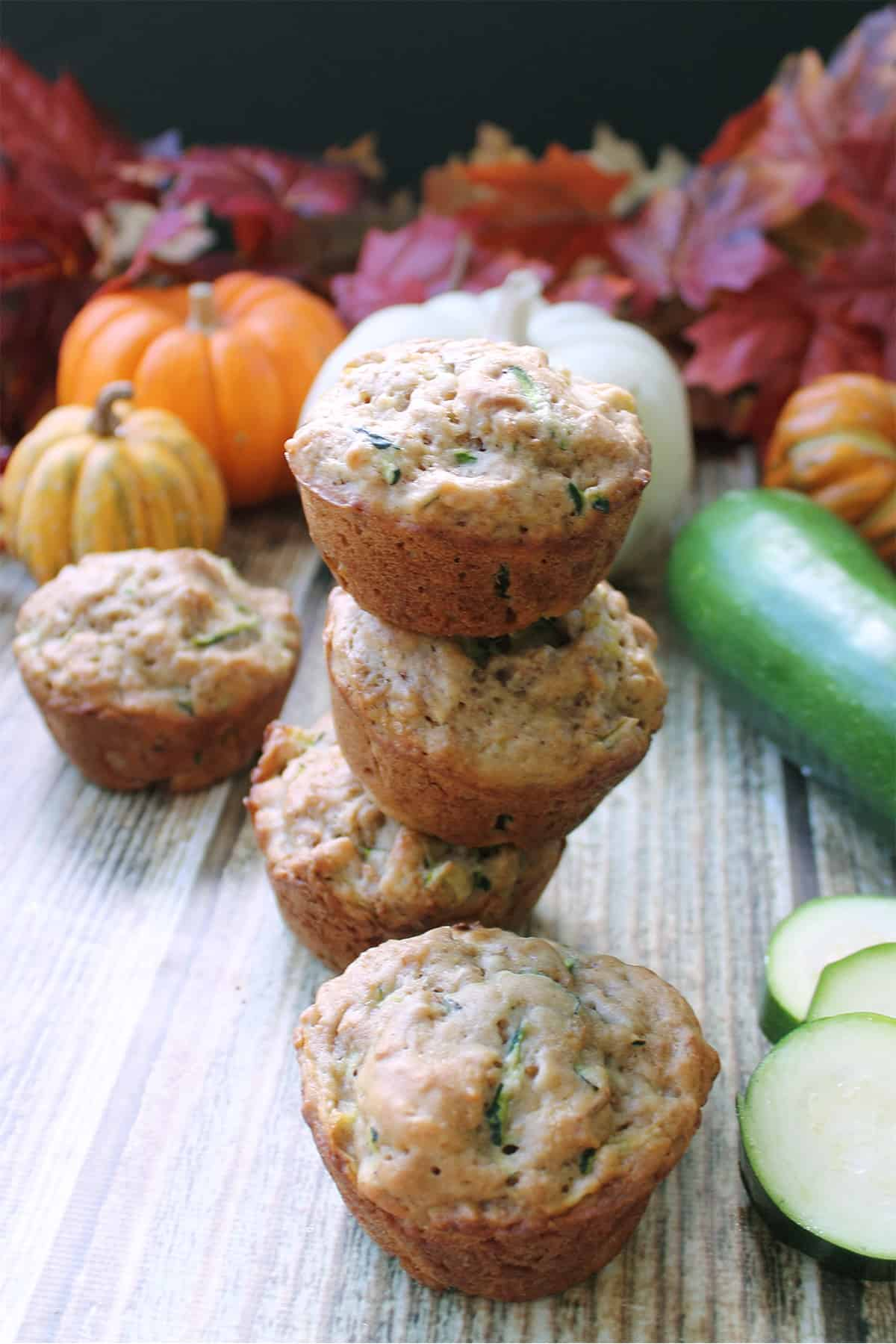 Stacked zucchini bran muffins on wooden table with fall leaves and pumpkin in back.