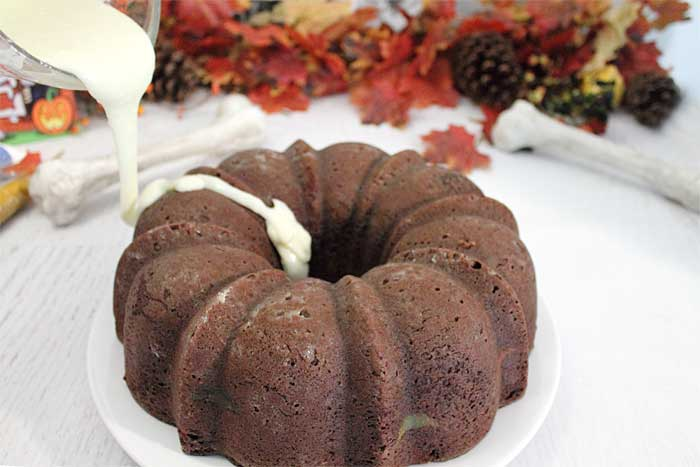 Chocolate Brown Sugar Bundt Cake with Cheesecake Swirl pouring glaze