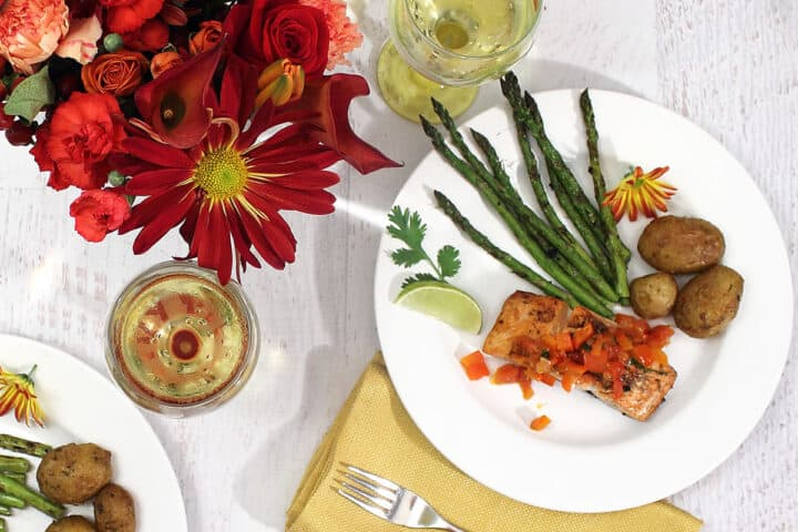Plated grilled salmon with red pepper sauce dinner with sides of potatoes and asparagus and a glass on white wine.