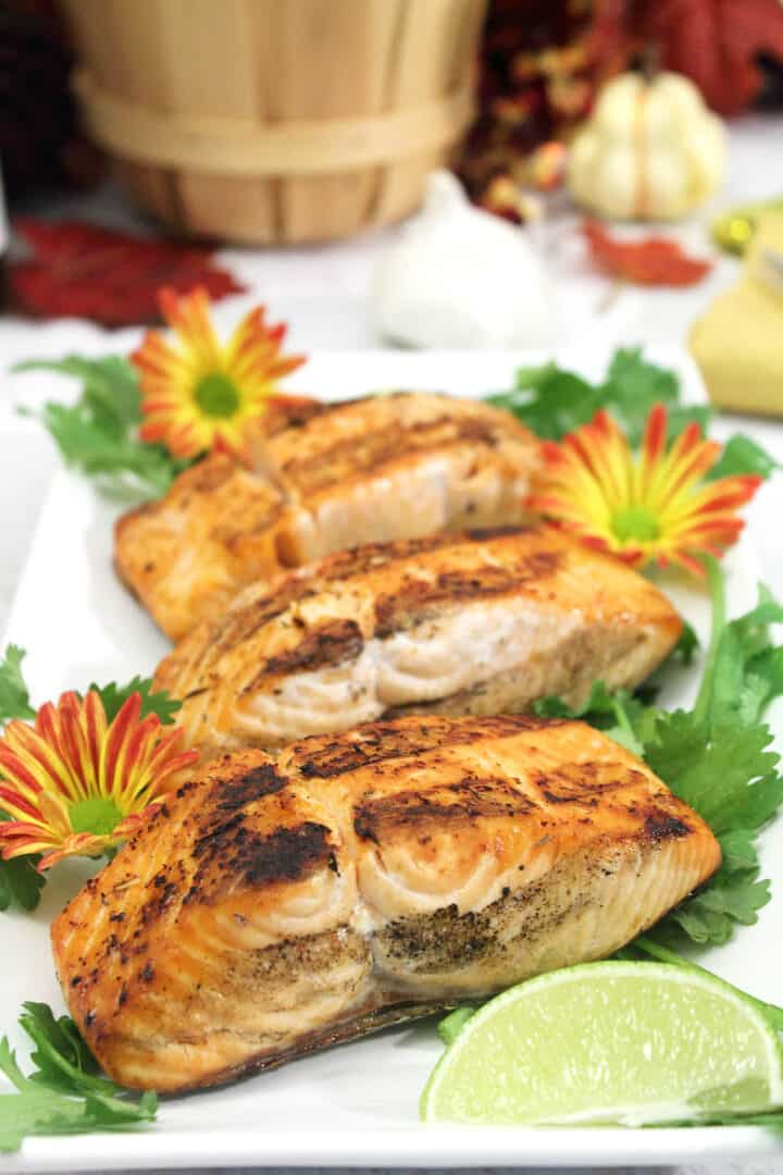 Grilled salmon on white platter with lime wedge and flowers.
