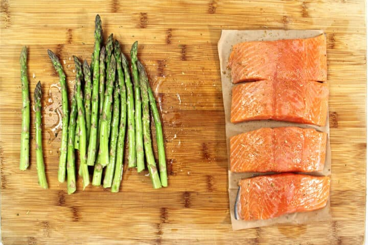 Seasoned salmon on wooden cutting board with asparagus.