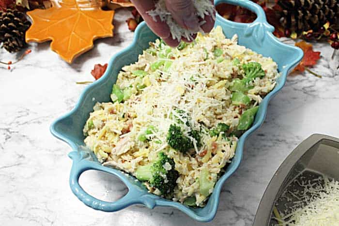 Cheesy Cauliflower Chicken Broccoli Casserole sprinkling cheese