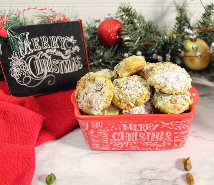 Pistachio cookies in red Christmas dish with Merry Christmas sign in background.