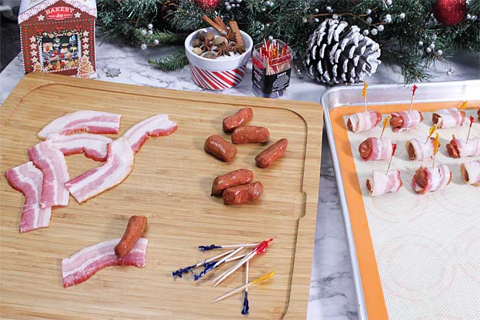 Ingredients laid out on cutting board with some smokies wrapped on cookie sheet.