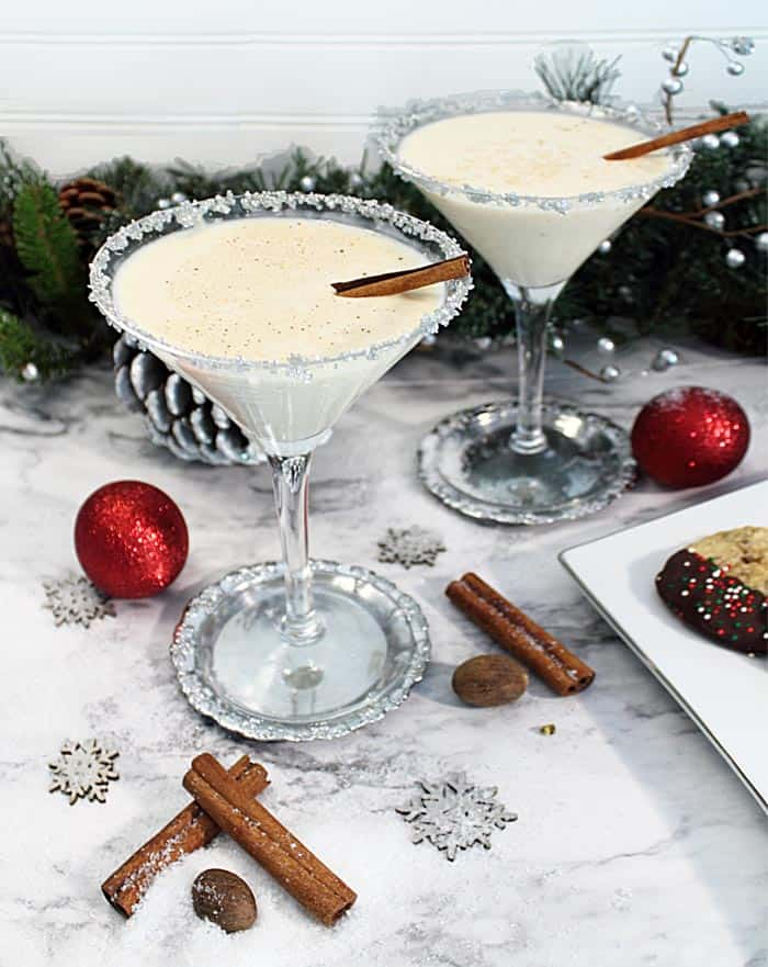 Eggnog martinis on a white marble table garnished with silver rim and cinnamon stick.