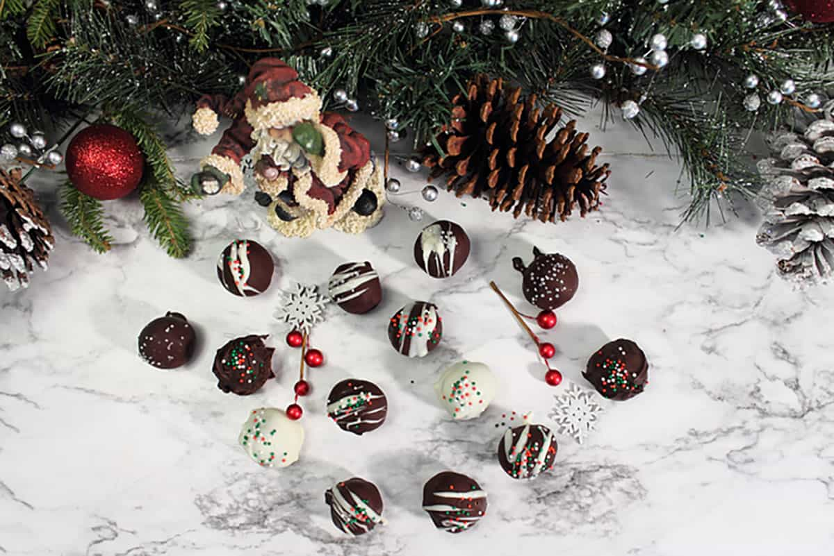 Overhead of chocolate drizzled truffles on white table with santa and greenery.