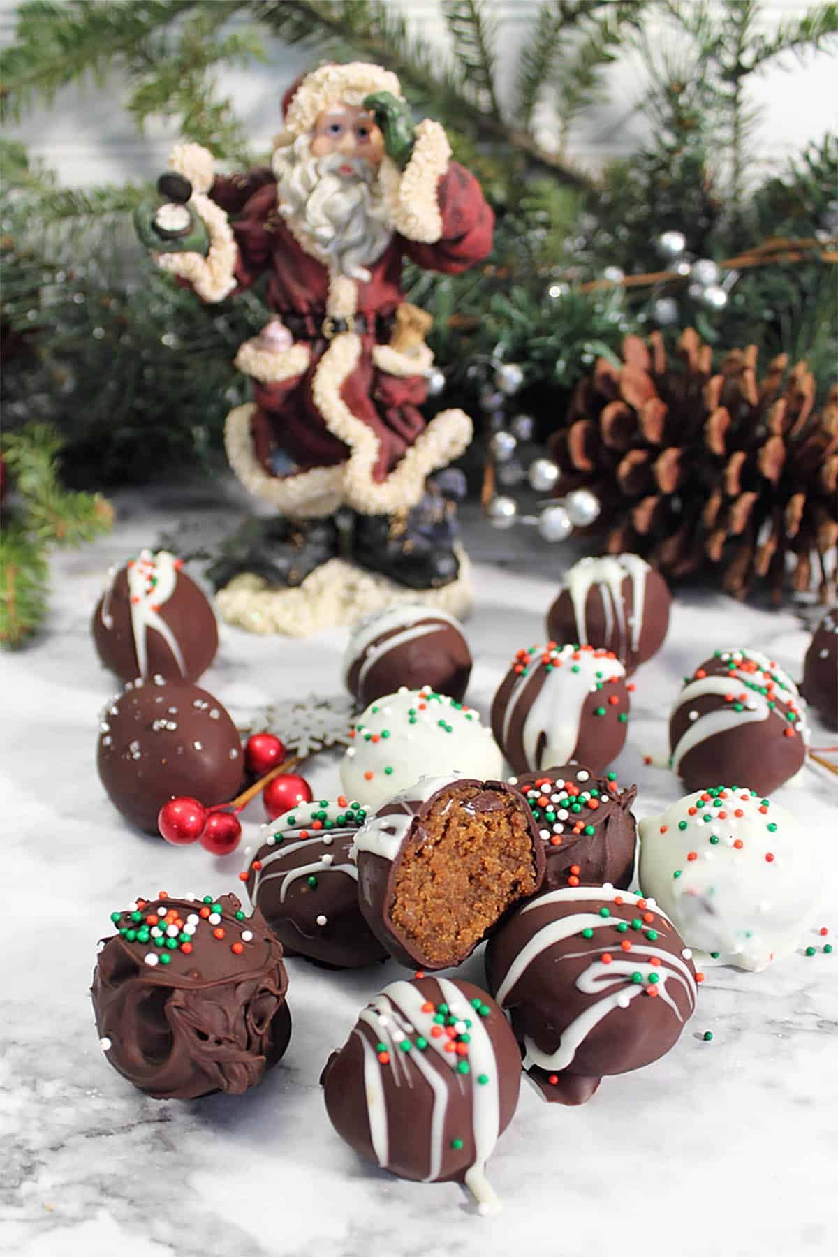 Truffles scattered on white table with santa, pinecone and greenery in background.