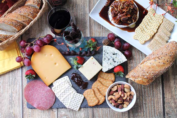 Cheese board featuring kahlua pecan baked brie with crackers.