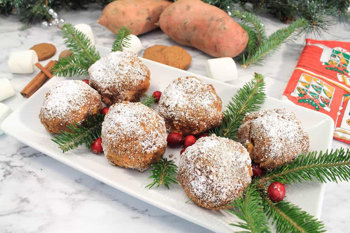 Plated sweet potato puffs with cranberries and pine garnish.
