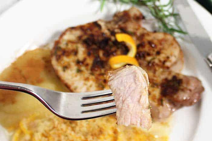 Bite of pork chop over dinner plate.