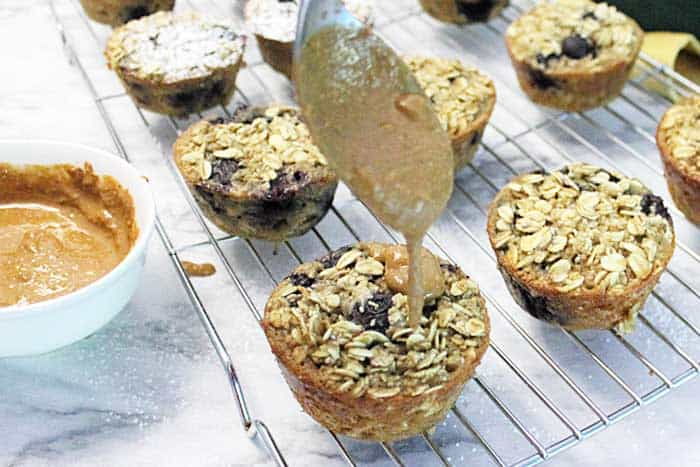 Blueberry Yogurt Oatmeal Muffins drizzling with almond butter