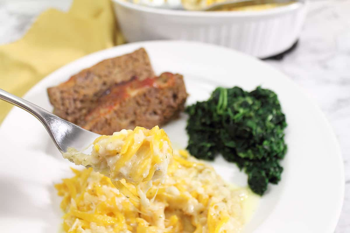 Plated squash bake with meatloaf and spinach.