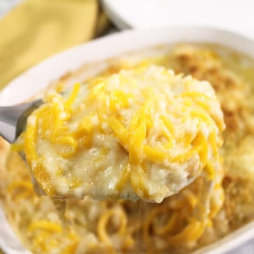 Spoonful of mac and cheese over casserole.