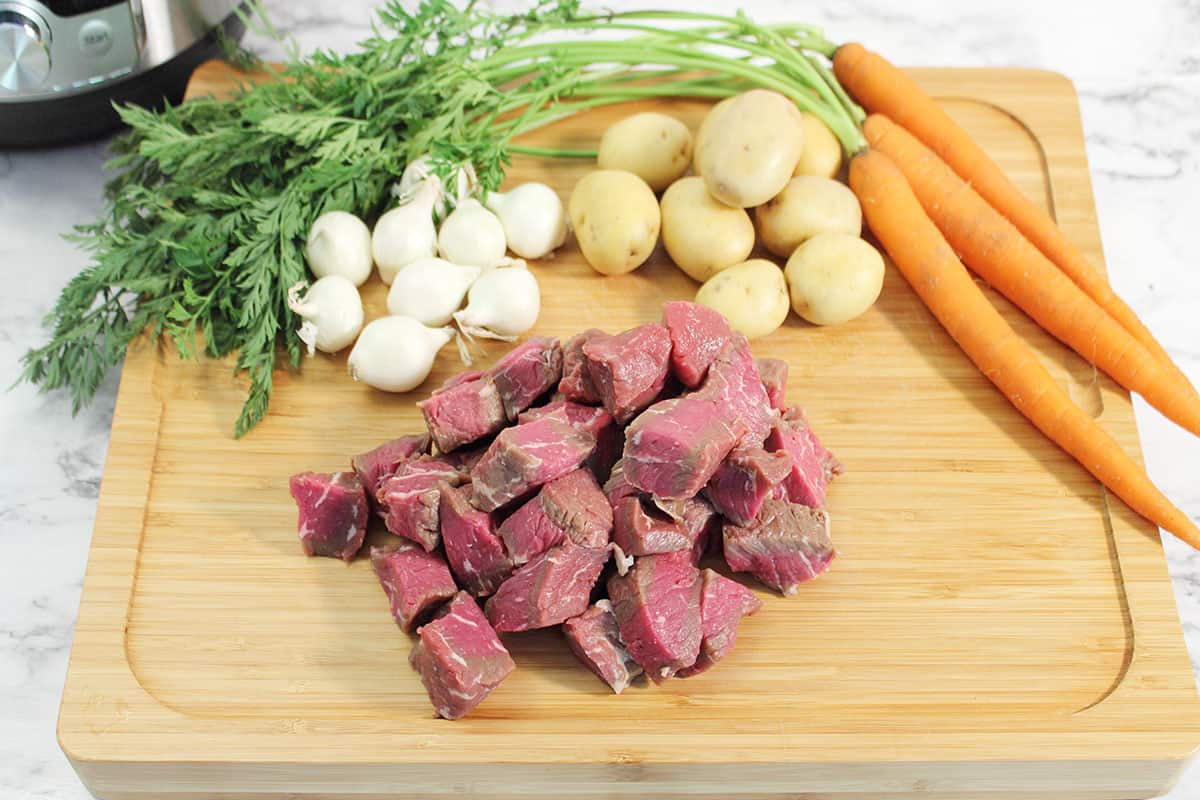 Ingredients for stew on cutting board.