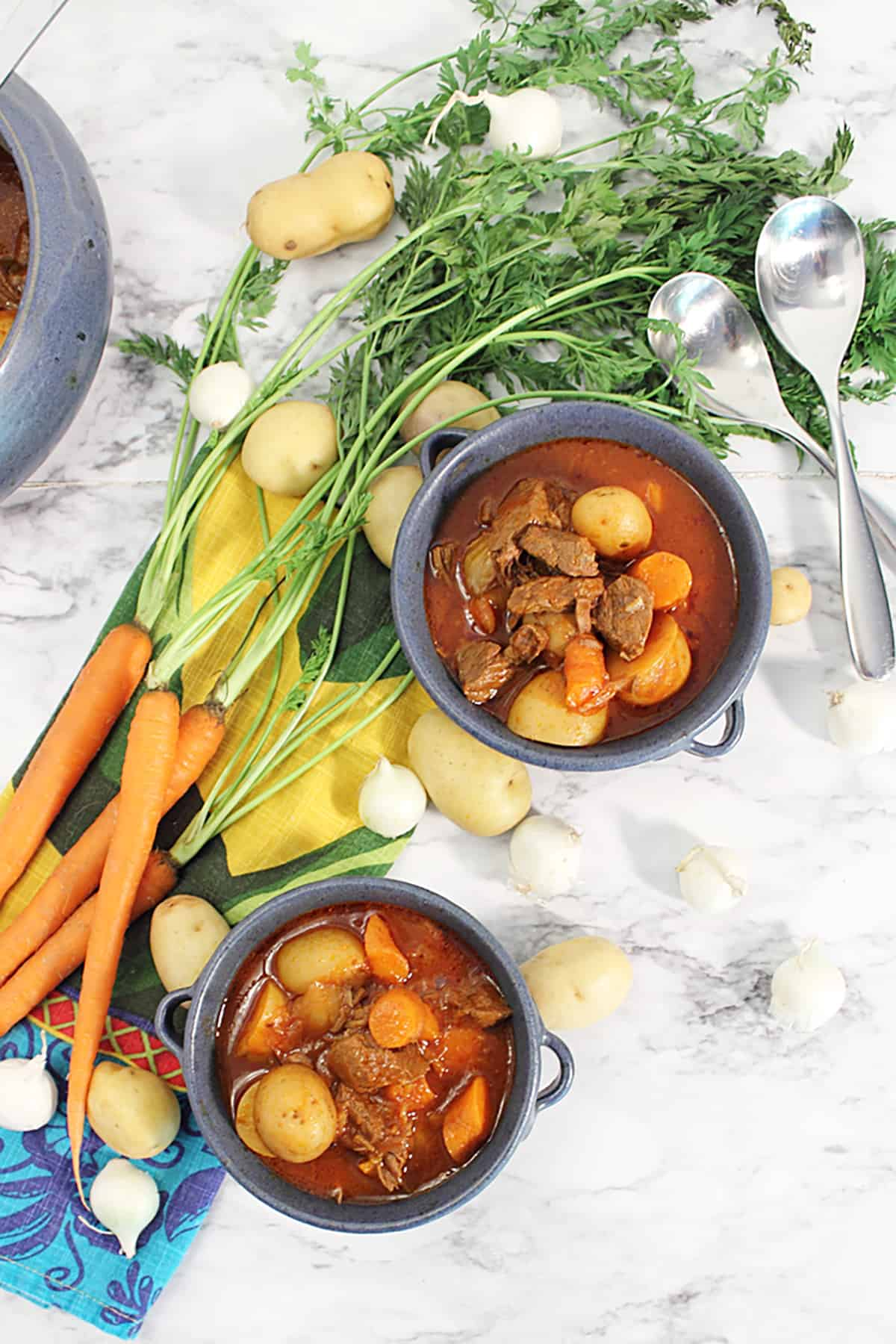Overhead of two blue bowls of stew with carrots beside them.