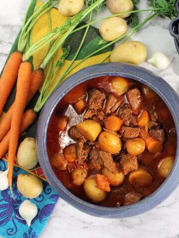 Overhead of stidfado in blue bowl with carrots and potatoes around it.