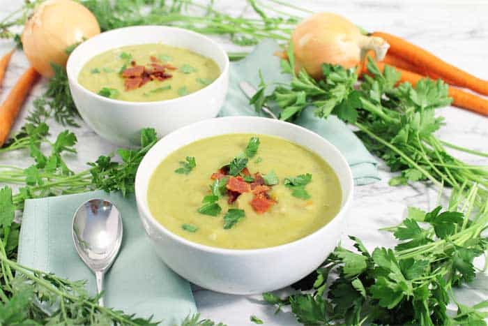 2 bowls of split pea soup on white table with greens onions and carrots around it.