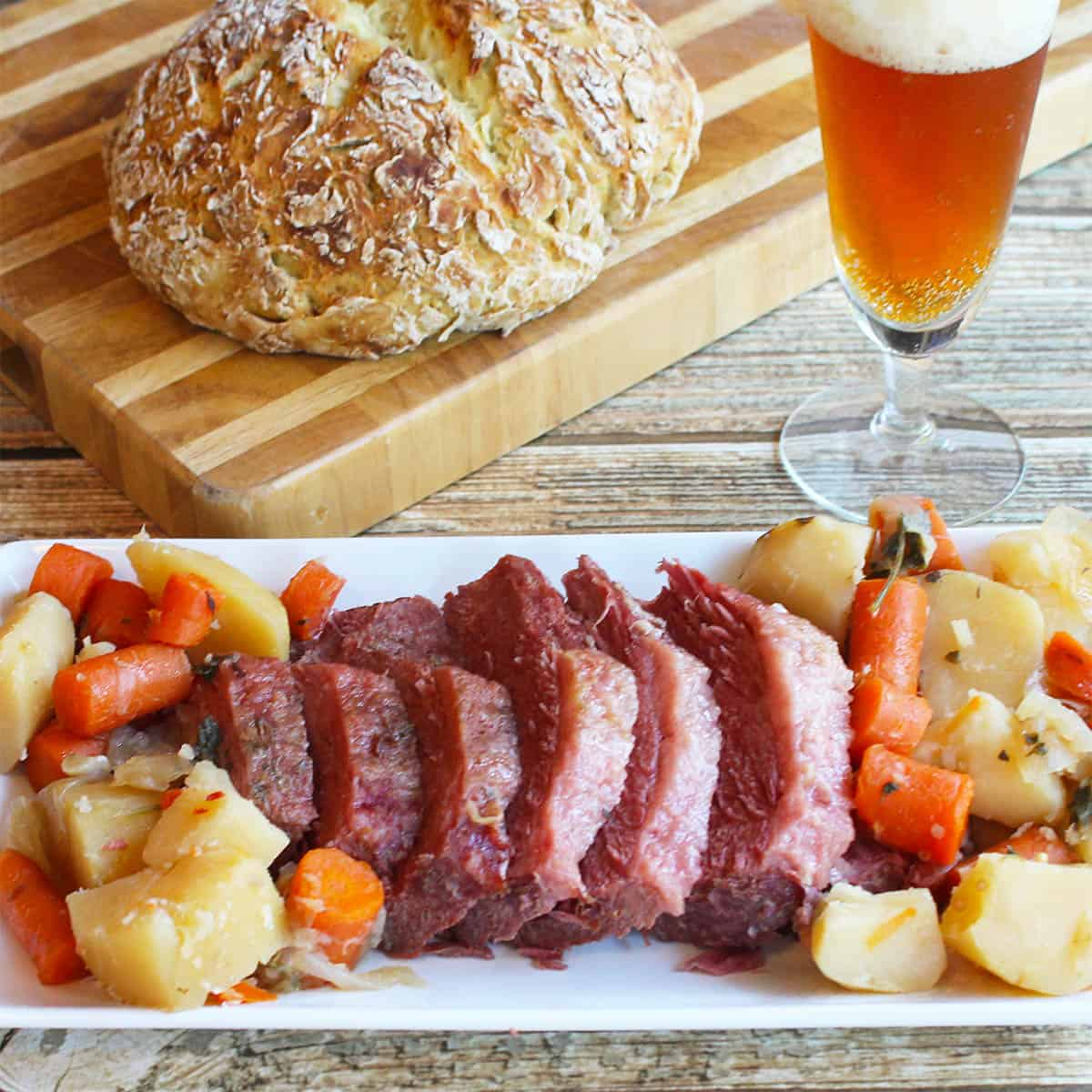 Corned beef dinner on platter with beer and Irish soda bread in background.