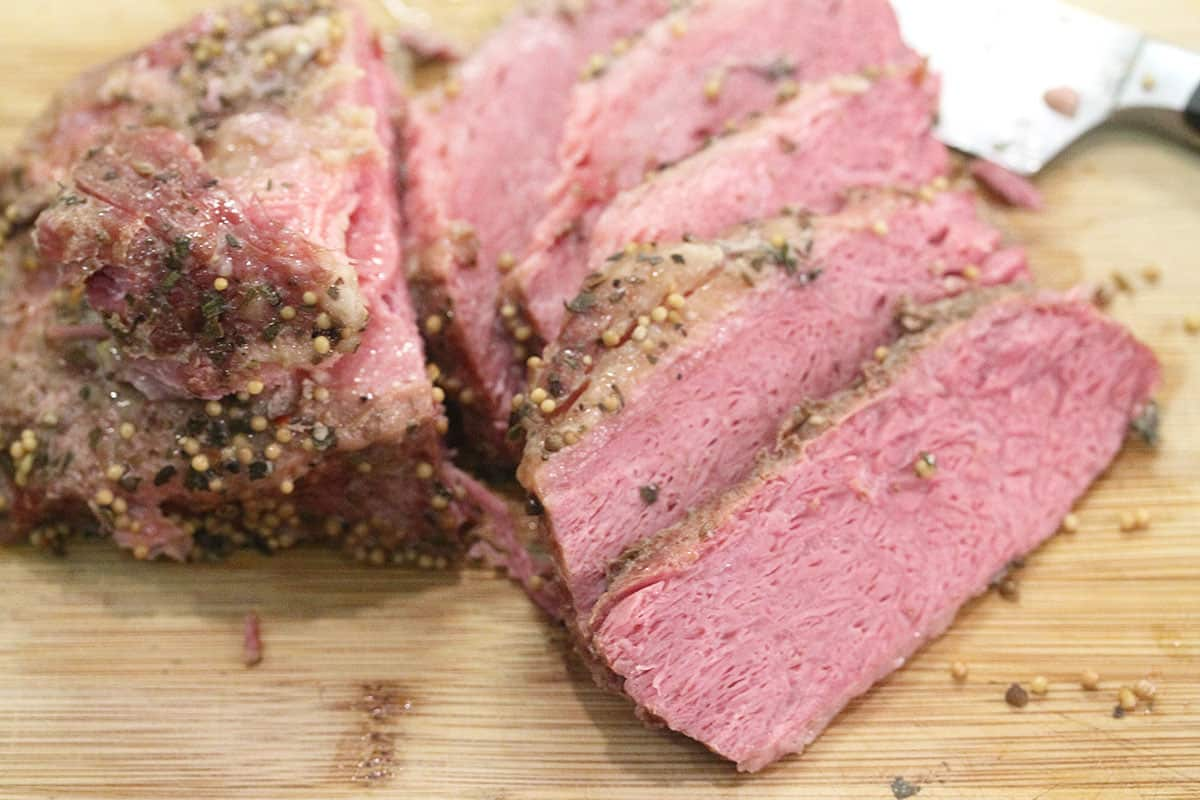 Closeup of sliced corned beef on cutting board.