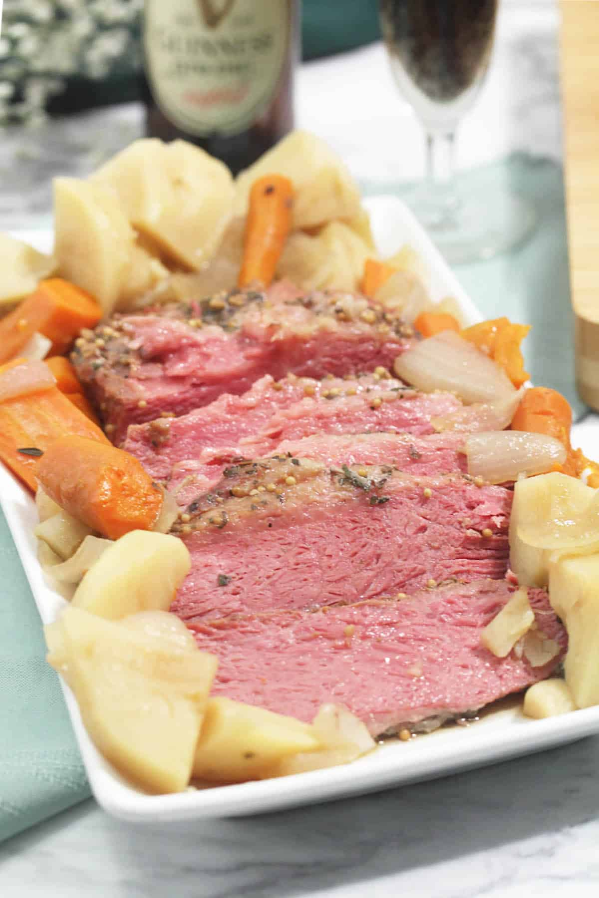 Siced corned beef surrounded by potatoes and vegetables on white platter.