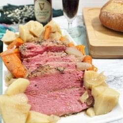 Siced corned beef surrounded by potatoes and vegetables on white platter with beer in background.