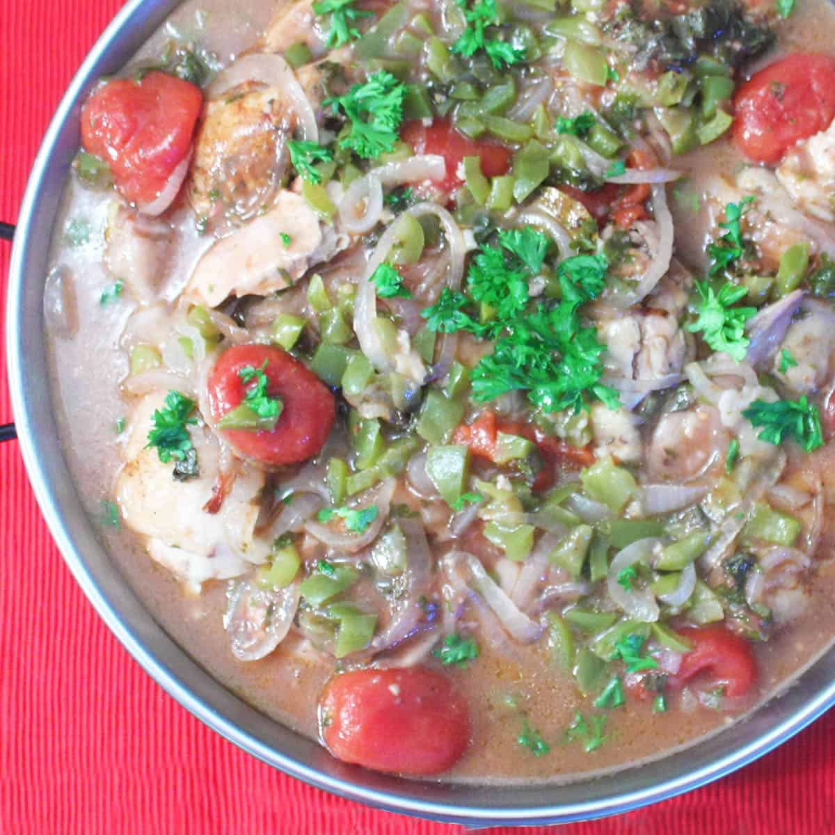 Overhead of large bowl with chicken cacciatore garnished with parsley.