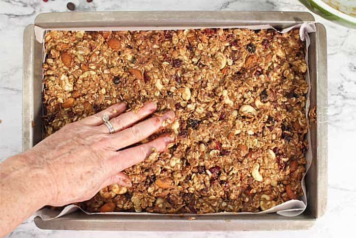 Patting trail mix granola mixture into pan