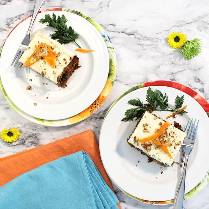 Overhead of two slices of carrot cake on white plates with orange and turquoise napkins.