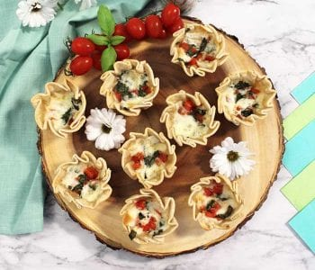 Baked empanadas overhead with tomatoes and daisies square