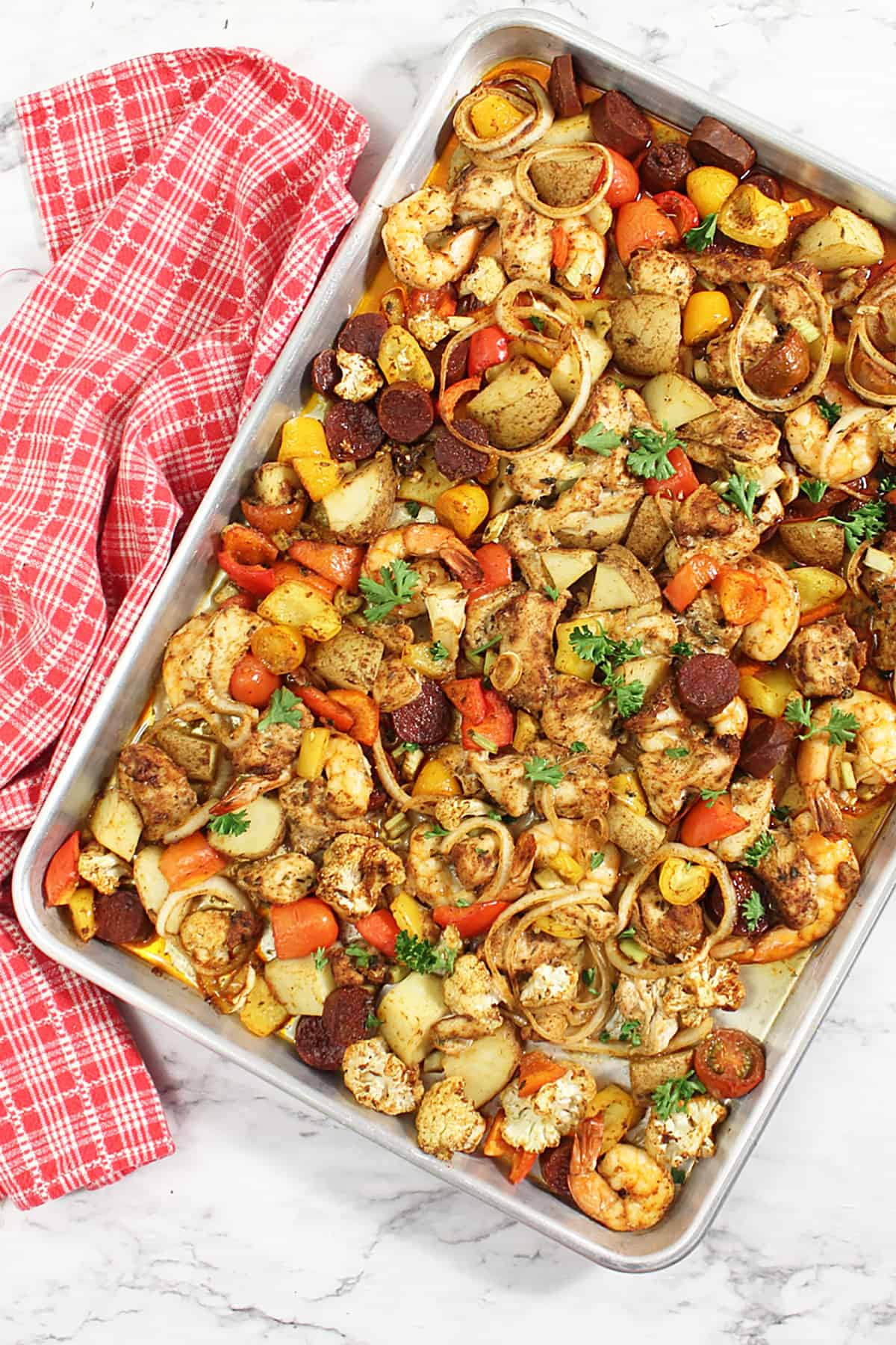 Overhead of creole chicken and shrimp sheet pan dinner on cookie sheet.