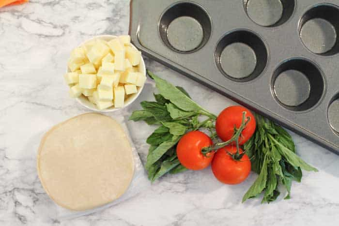 Tomatoes, basil, cubed mozzarella and empanada discs on table by muffin pan