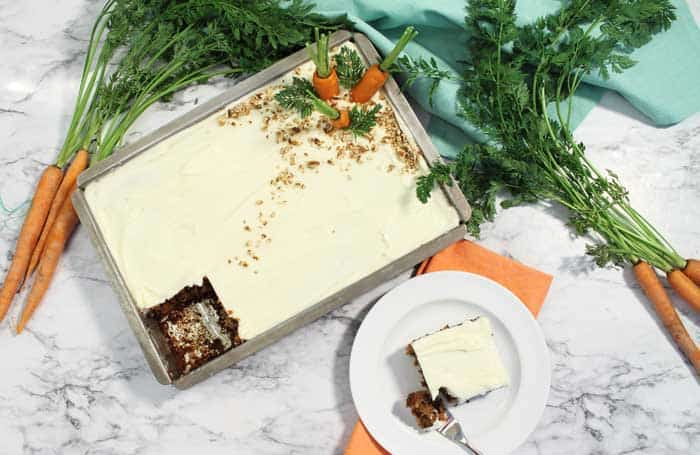 Carrot Cake with slice out on white plate overhead