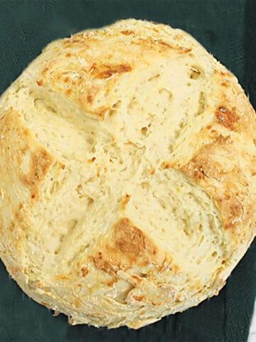 Overhead of fresh baked bread on green napkin.