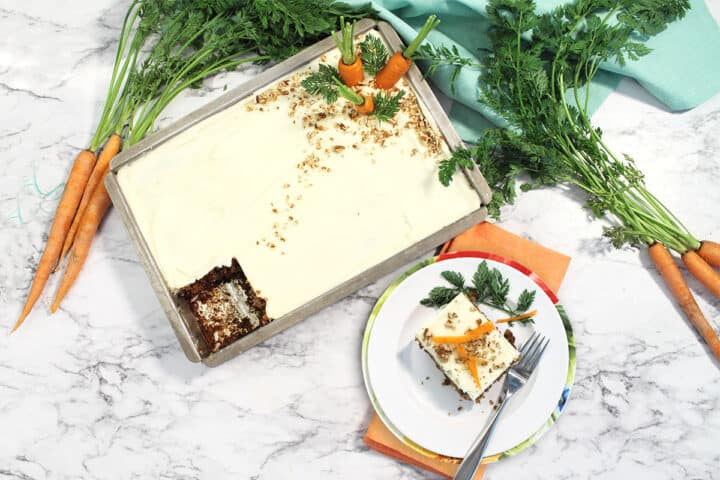 Overhead of whole carrot cake with slice next to it.