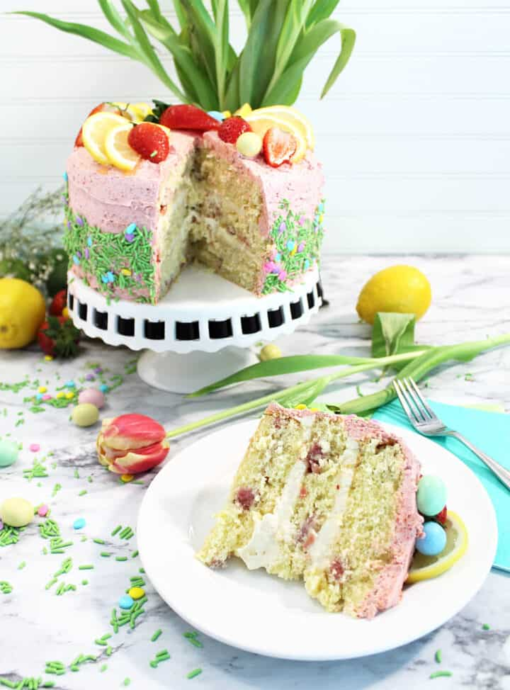 Decorated Strawberry Lemon Cake on cake stand with slice in front.