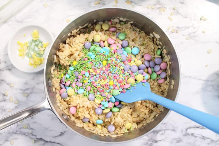 Adding in pastel m&ms candy and sprinkles to the bowl.