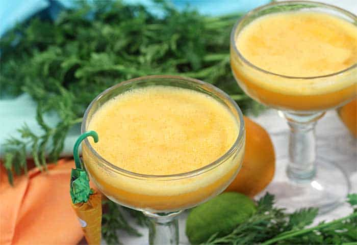 closeup of 2 margaritas with carrot greenery and pastel napkins