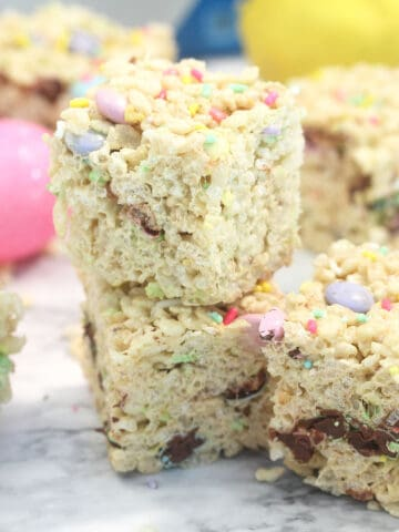 Double stack of Easter rice krispie treats with colorful eggs around them.