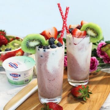 Two garnished smoothies on wooden board.
