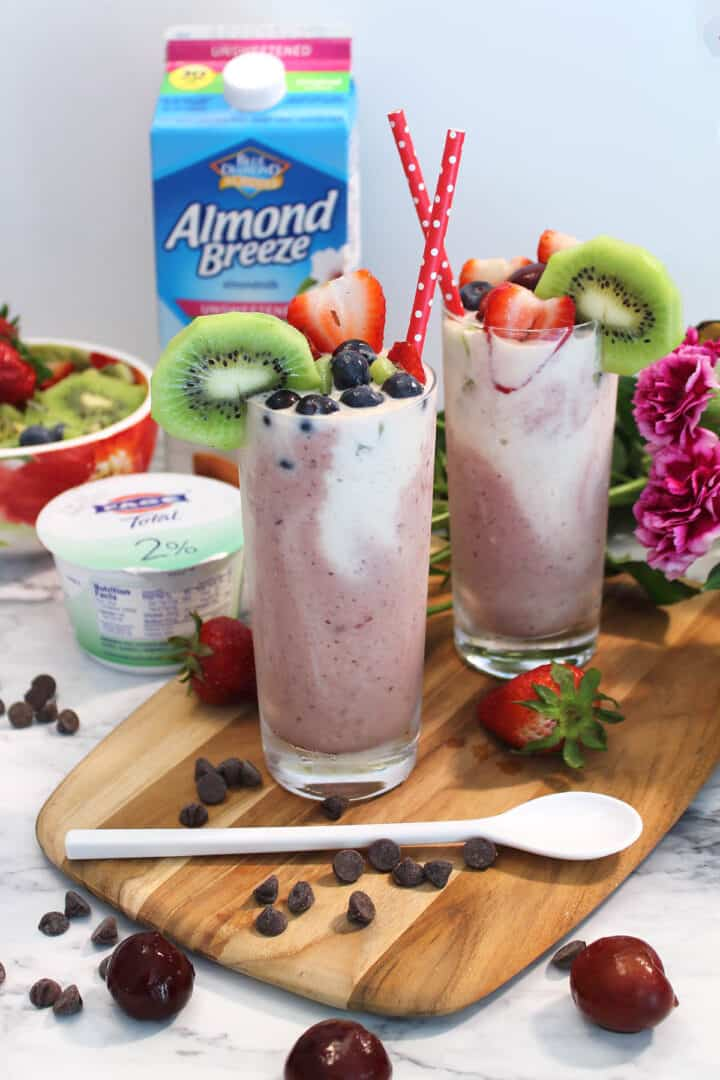 Two smoothies with chocolate chips around them and flowers in back.