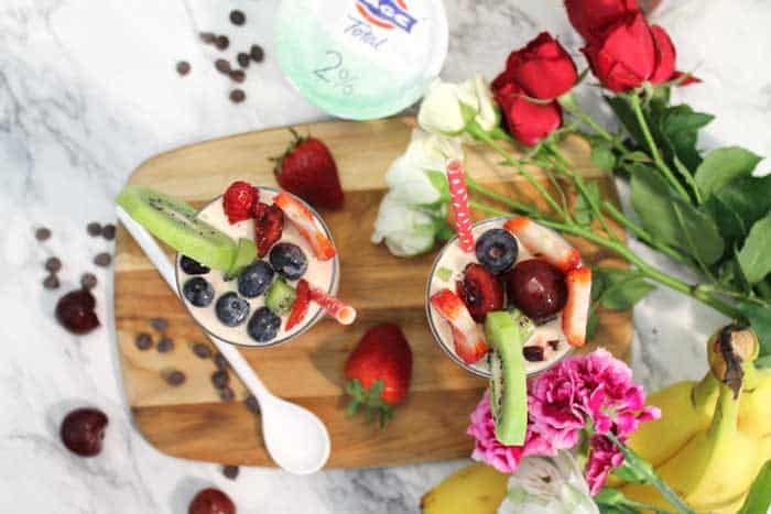 Cherry Vanilla Smoothie on wooden board with flowers and Fage yogurt container overhead