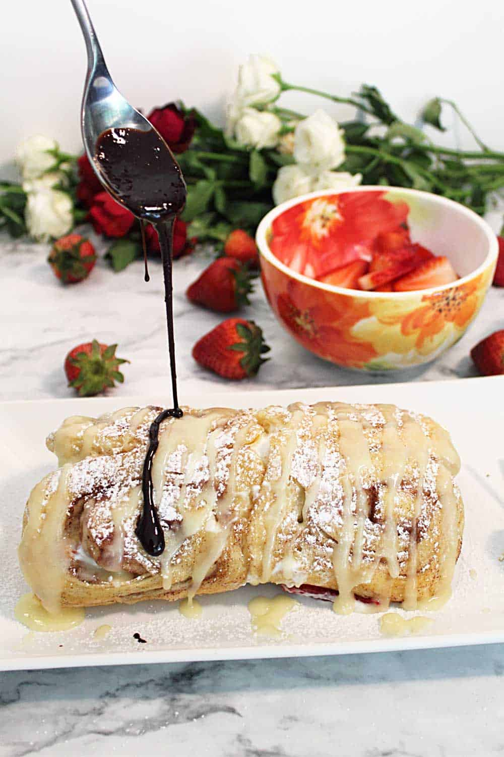 Drizzling chocolate on strawberry cinnamon roll