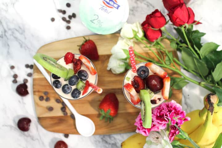 Overhead of cherry vanilla smoothies on wooden board with fruit garnish.
