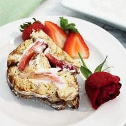 Strawberry Cinnamon Roll slice on white plate with rose