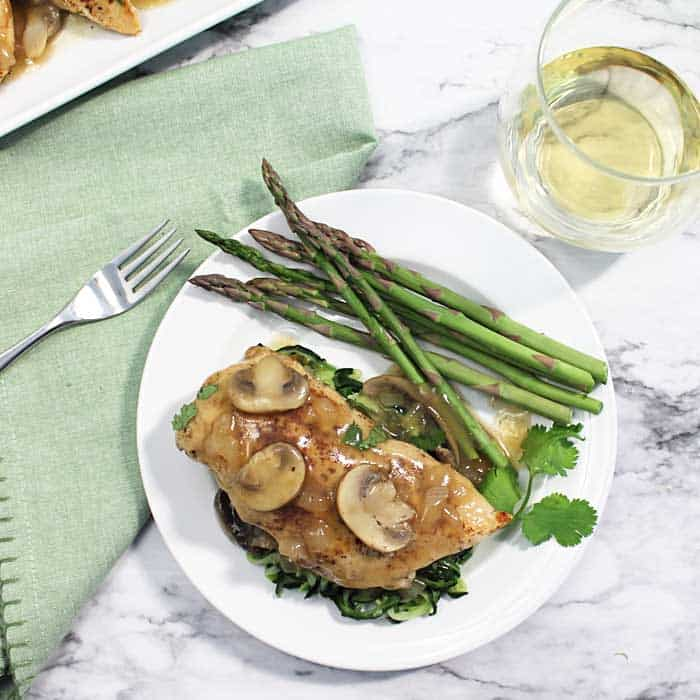 Chicken Chablis with Mushrooms and Asparagus on a White Plate.