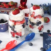 2 Patriotic Parfaits ready to serve with colored spoons and berries around.